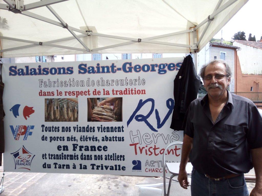Georges Muniesa junto a la publicidad de su puesto. Saint Gervais sur Mare